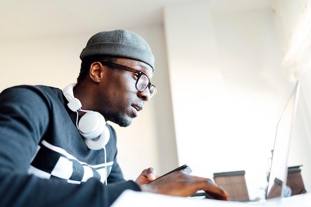 Hombre en casa con teléfono inteligente y computadora portátil