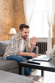 Hombre en casa con videollamada con familia