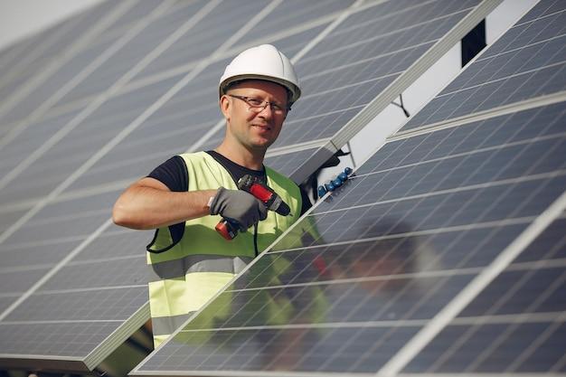 Hombre con casco blanco cerca de un panel solar