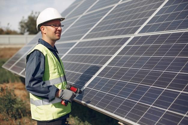 Hombre en un casco blanco cerca de un panel solar