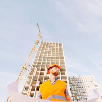 Hombre en casco con blueprint