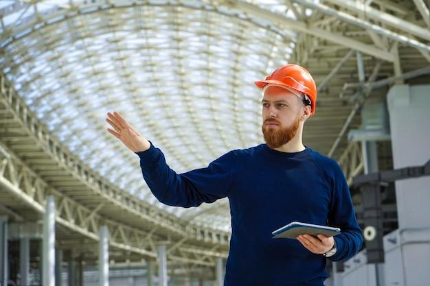 Un hombre en un casco en un gran espacio con una tableta