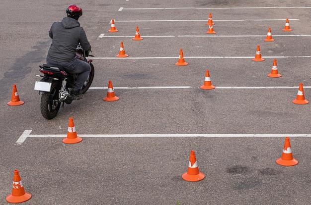 Hombre en casco en moto haciendo ejercicios en aparcamiento entre conos de tráfico naranja