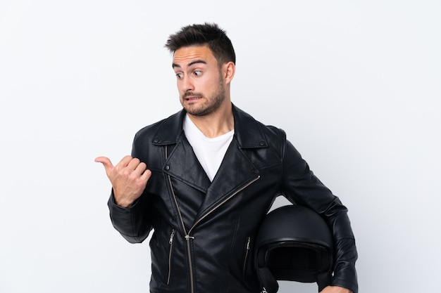 Hombre con casco de moto infeliz y apuntando hacia un lado
