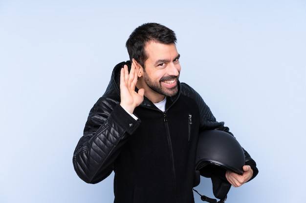 Hombre con casco de moto sobre pared aislada escuchando algo poniendo la mano en la oreja