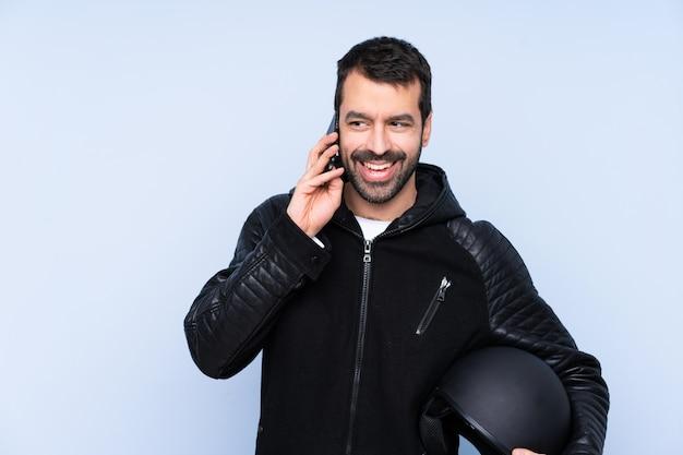 Hombre con casco de moto sobre pared aislada manteniendo una conversación con el teléfono móvil