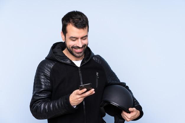 Hombre con casco de moto sobre pared aislada