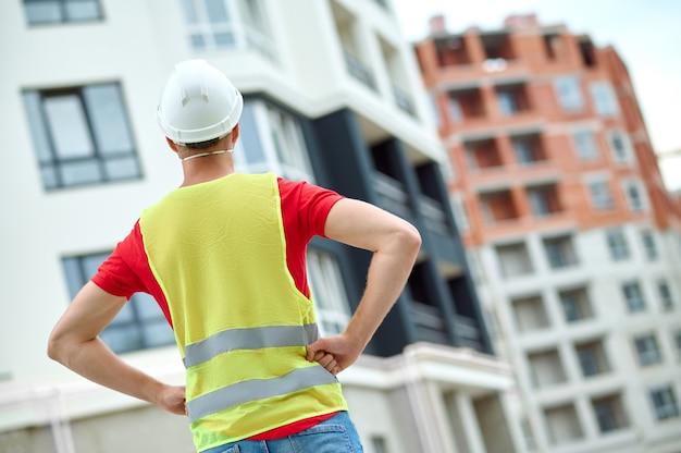 Hombre en un casco de pie ante una estructura construida