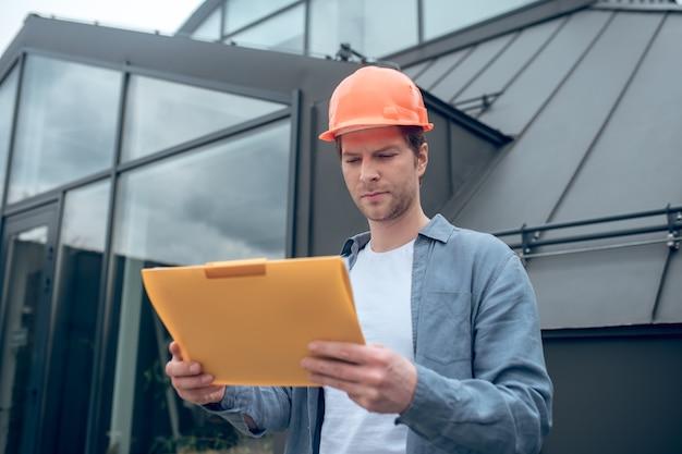 Hombre en casco protector mirando de cerca el documento