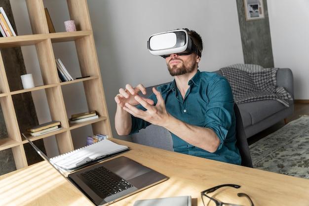 Hombre con casco de realidad virtual en casa con portátil
