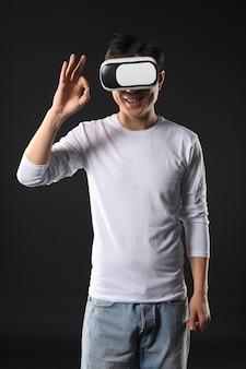 Hombre con casco de realidad virtual que muestra signo ok