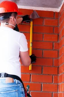 Un hombre en un casco y un respirador realiza trabajos de pintura en un techo de concreto