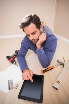 Hombre casual acostado en el piso usando tablet pc para instrucciones de bricolaje