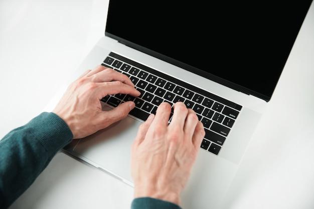 Hombre casual escribiendo en un teclado de computadora portátil