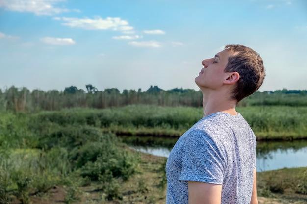 Hombre casual feliz respirando aire fresco en un campo con lago de fondo