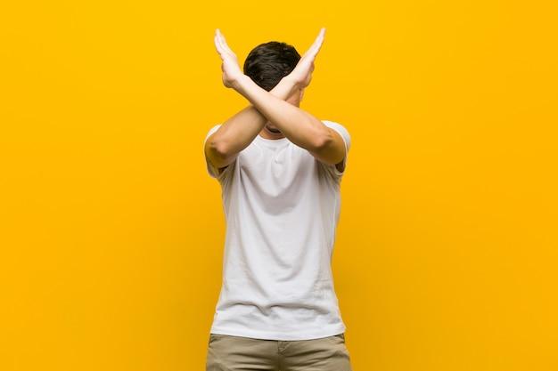 Hombre casual hispánico joven que mantiene dos brazos cruzados, concepto de la negación.