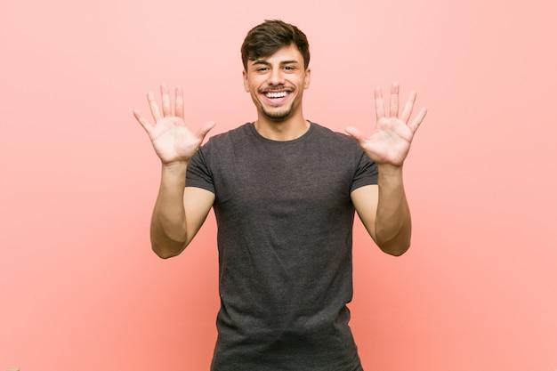 Hombre casual hispánico joven que muestra el número diez con las manos.