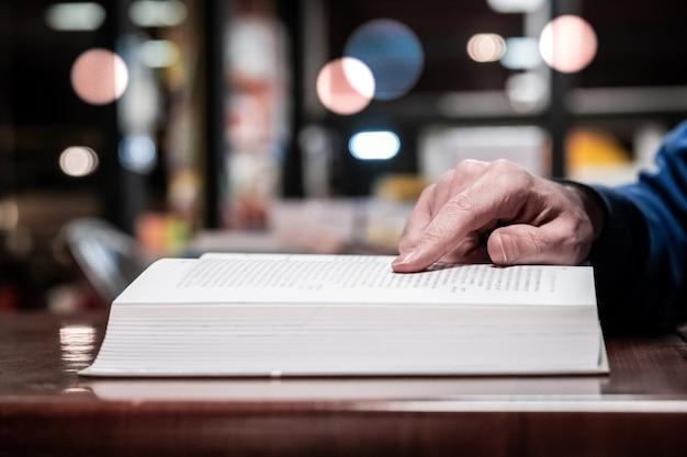 Hombre casual leyendo libro sobre mesa de madera en la biblioteca, estilo vintage