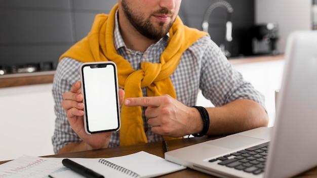 Hombre casual de primer plano sosteniendo teléfono móvil