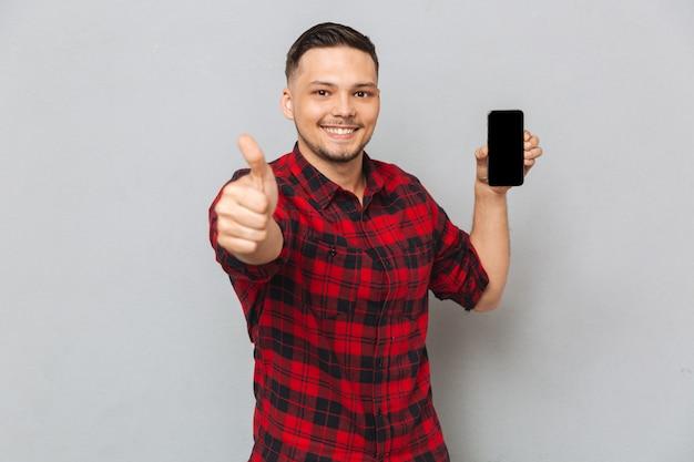 Hombre casual sonriente feliz que sostiene el teléfono móvil de la pantalla en blanco