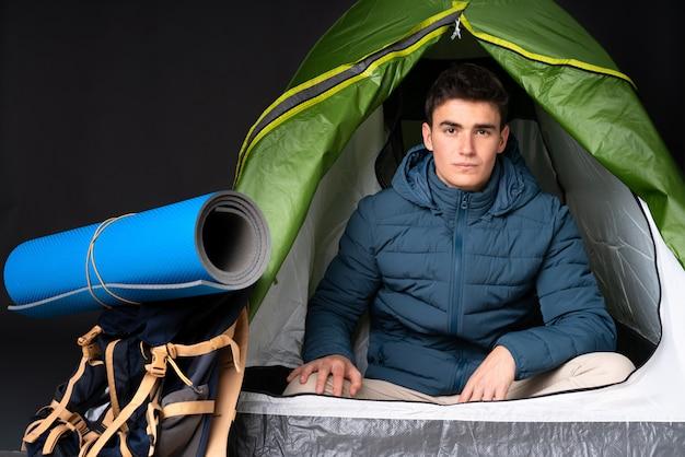 Hombre caucásico adolescente dentro de una tienda de campaña verde aislada en negro con expresión triste y deprimida