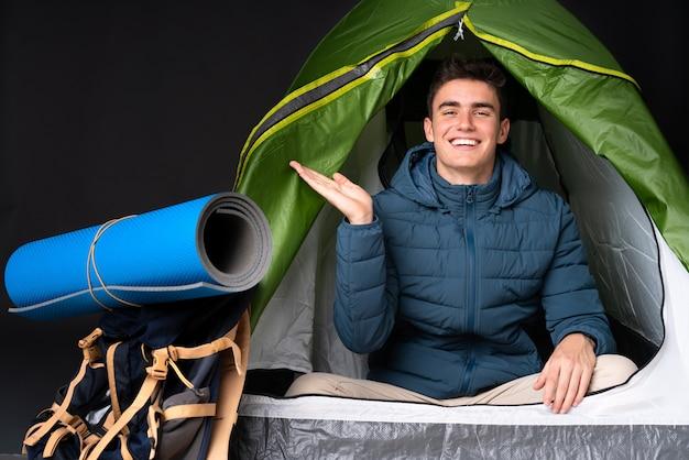 Hombre caucásico adolescente dentro de una tienda de campaña verde aislado en negro