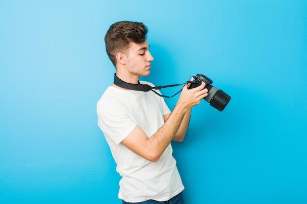 Hombre caucásico adolescente tomando fotos con una cámara réflex