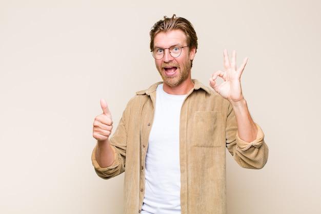 Hombre caucásico adulto rubio que se siente feliz, asombrado, satisfecho y sorprendido, mostrando gestos bien y pulgares arriba, sonriendo