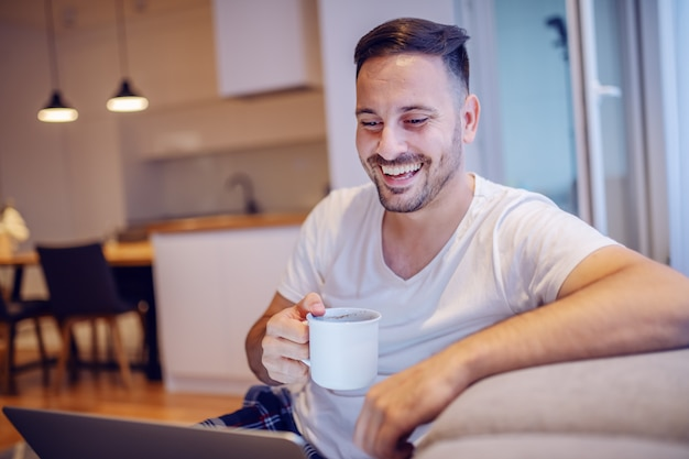 Hombre caucásico sin afeitar sonriente hermoso en pijama que se sienta en sala de estar con la computadora portátil en regazo y que bebe su café fresco de la mañana.