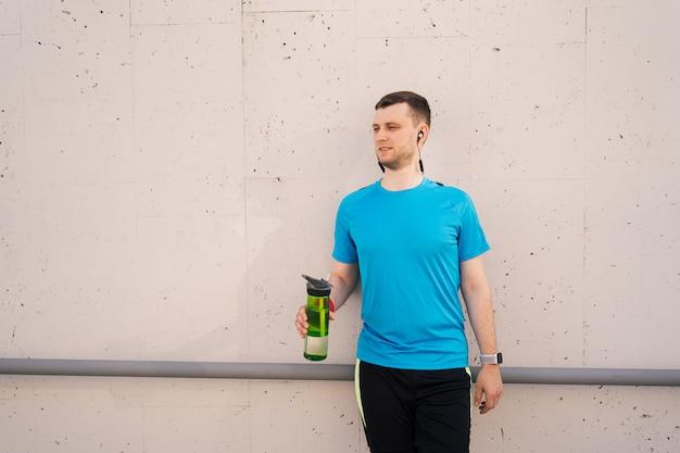 Hombre caucásico de agua potable durante los ejercicios