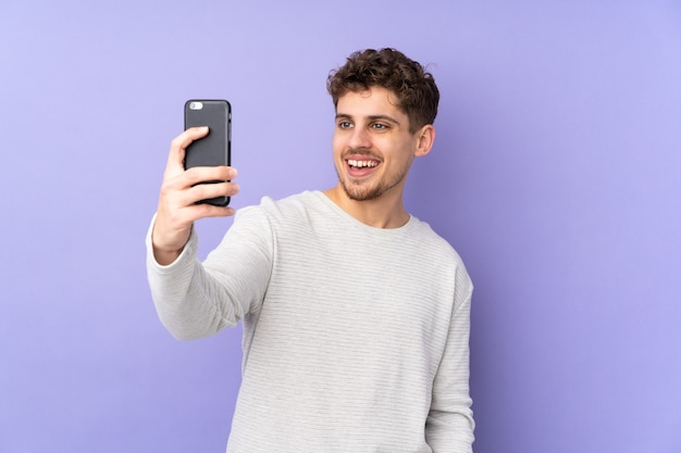 Hombre caucásico aislado en púrpura haciendo un selfie