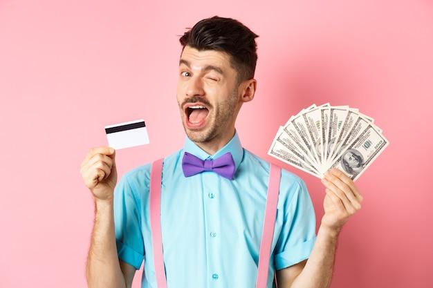 Hombre caucásico alegre en pajarita guiñando un ojo mostrando tarjeta de crédito plástica y dinero recomendando s ...