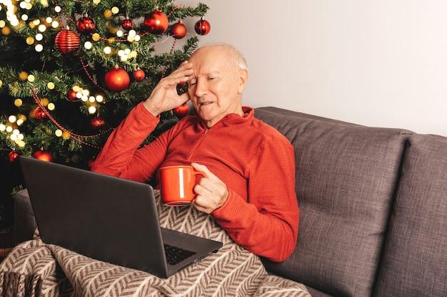 Hombre caucásico anciano solitario triste con portátil sentado en un sofá cerca de un árbol de navidad con taza de té charlando con familiares en línea. autoaislamiento, estado de ánimo de vacaciones.