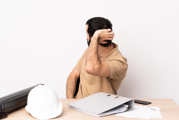 Hombre caucásico arquitecto con barba en una mesa en posición trasera y pensando.
