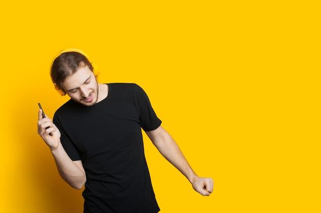Hombre caucásico bailando con cabello largo y barba escuchando música con teléfono y auriculares en una pared amarilla con espacio libre