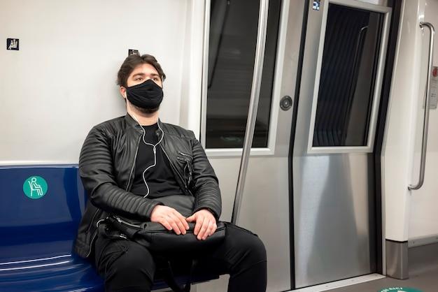 Un hombre caucásico con barba y auriculares en máscara médica negra sentado en una silla en el metro