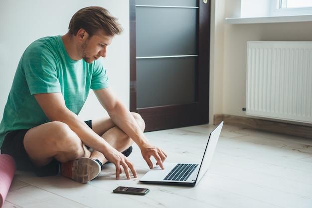 Hombre caucásico con barba y cabello rubio sentado en el piso y usando una computadora portátil antes de practicar yoga con una alfombra especial