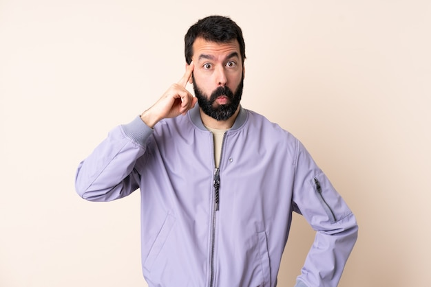 Hombre caucásico con barba con una chaqueta sobre espacio aislado pensando en una idea