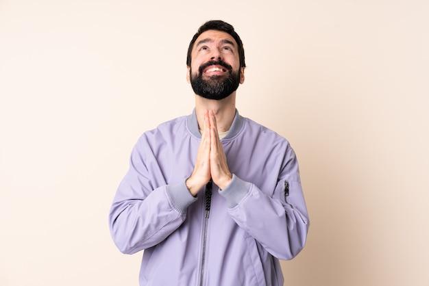 Hombre caucásico con barba con una chaqueta sobre la pared mantiene la palma unida