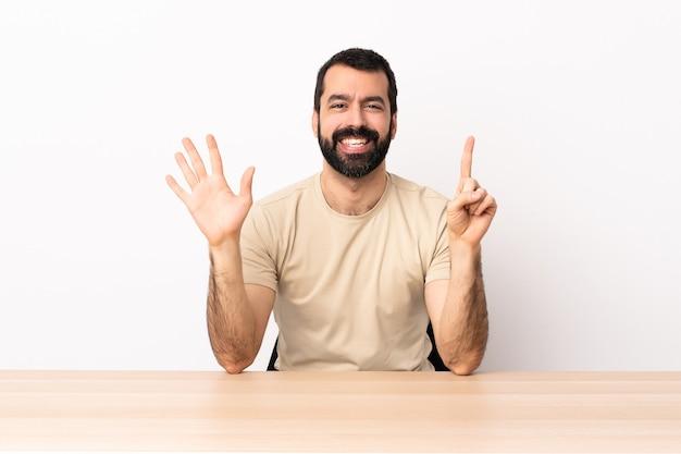 Hombre caucásico con barba en una mesa contando seis con los dedos.