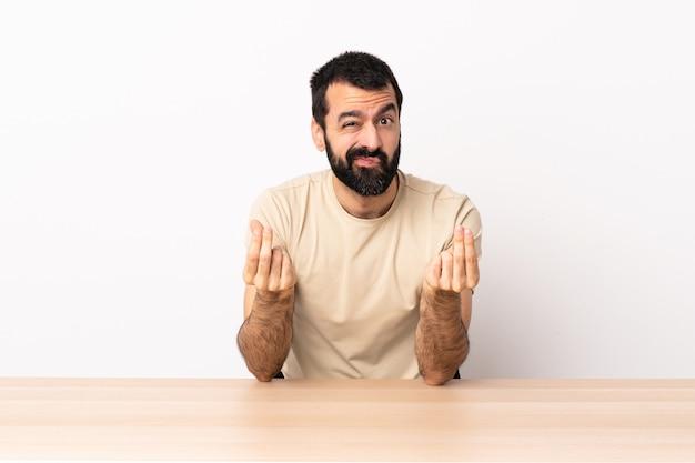 Hombre caucásico con barba en una mesa haciendo dinero gesto pero está arruinado
