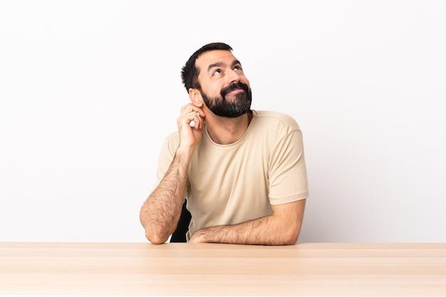 Hombre caucásico con barba en una mesa pensando en una idea.