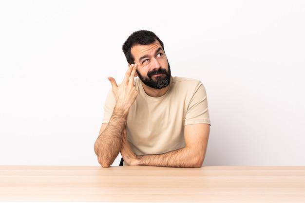 Hombre caucásico con barba en una mesa con problemas para hacer gestos de suicidio.