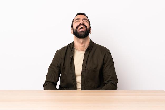 Hombre caucásico con barba en una mesa riendo.
