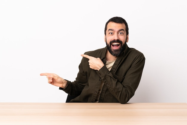 Hombre caucásico con barba en una mesa sorprendida y apuntando hacia el lado.