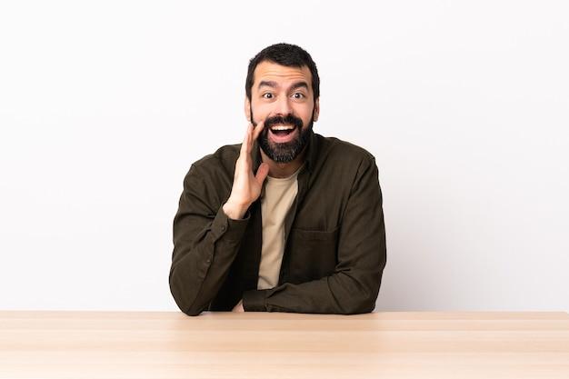Hombre caucásico con barba en una mesa con sorpresa y expresión facial conmocionada.