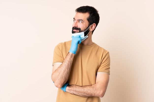 Hombre caucásico con barba protegiendo con una máscara y guantes sobre la pared pensando una idea mientras mira hacia arriba