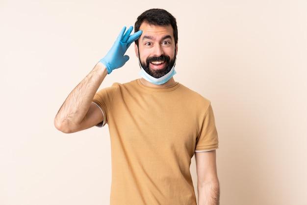 El hombre caucásico con barba que protege con una máscara y guantes sobre la pared se ha dado cuenta de algo y tiene la intención de encontrar la solución.