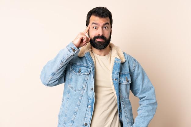 Hombre caucásico con barba sobre espacio aislado pensando una idea