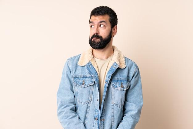 Hombre caucásico con barba sobre espacio aislado teniendo dudas mientras mira hacia arriba